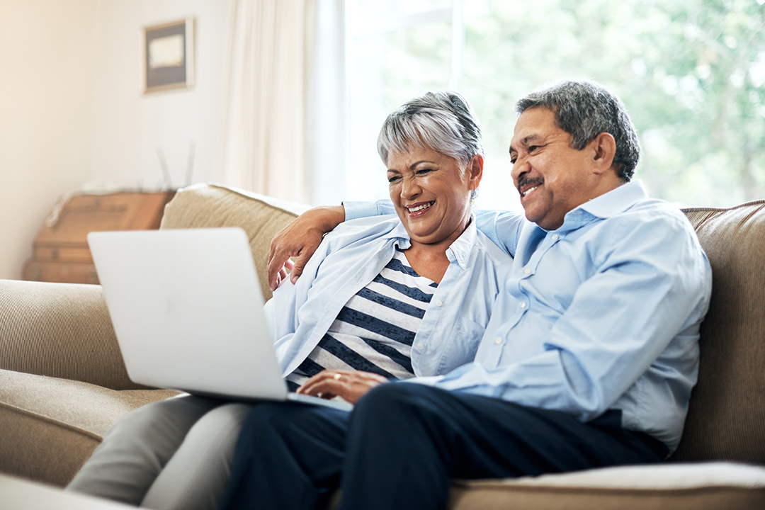 Couple on lounge with laptop